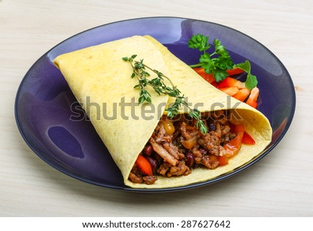 Burrito with herbs on the wood background - stock photo