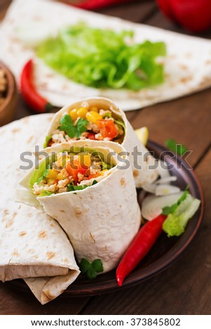 Burritos wraps with chicken meat, corn, tomatoes and peppers on wooden background - stock photo