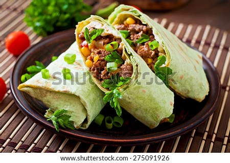 Burritos wraps with minced beef and vegetables on a wooden background - stock photo