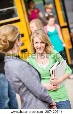 Bus: High School Student Talks To Principal On Way Into School - stock photo