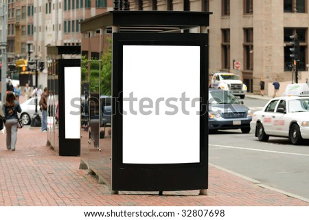 Bus stop billboard in USA city for outdoor advertising. Brick sidewalk, traffic, people in the background