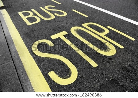 Bus stop sign with yellow paint on asphalt - stock photo