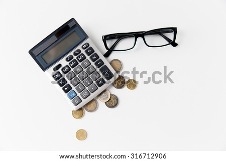 busines, finance, money and bookkeeping concept - calculator, eyeglasses and euro coins on office table - stock photo