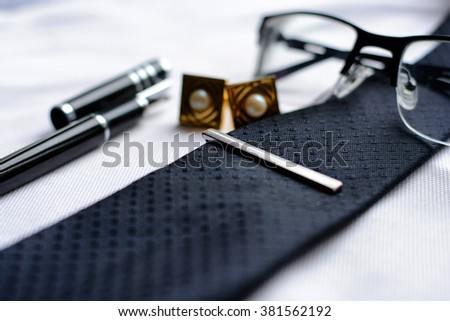 Business accessories (cufflinks, fountain pen, tablet, phone, glasses, notepad) in the men's classic white shirt with tie - stock photo