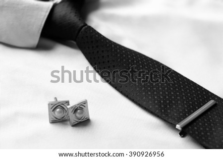 Business accessories (cufflinks, fountain pen, tablet, phone, glasses, notepad) in the men's classic white shirt with tie