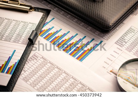 Business accessories (notebook, magnifier, calculator, planchette, tablet, fountain pen, notebook, glasses) and graphics, tables, charts on white sheets on office desk. Vignette, soft focus.
