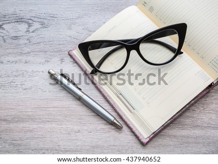 business accessories, notebook, pen and glasses on the desktop, business concept
