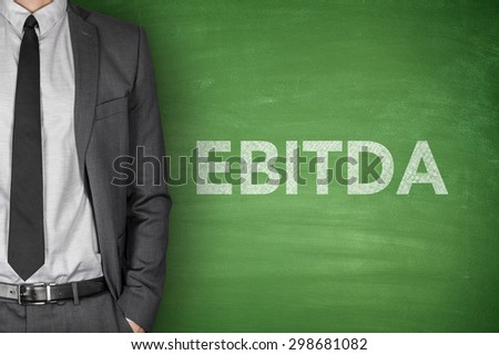 Business acronym EBITDA Earnings before interest and taxes depreciation and amortization on green blackboard with businessman - stock photo