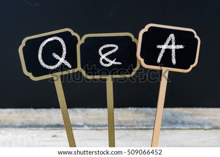 Business acronym Q&A as Questions and Answers written with chalk on wooden mini blackboard labels, defocused chalkboard and wood table in background