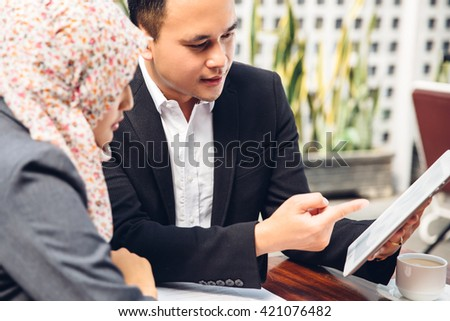 Business adviser analyzing financial figures of the company while meeting - stock photo