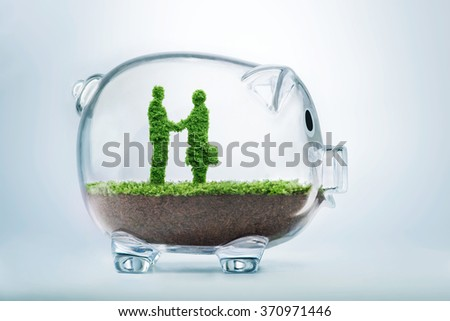 Business agreement concept with grass growing in shape of two businessmen shaking hangs inside transparent piggy bank