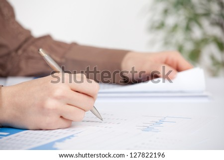 Business analysis - sheet, graph, (business report) and analyst. Selective focused on pen.