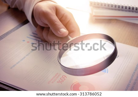 Business analytics and statistics. Businessman study report using a magnifying glass.  - stock photo