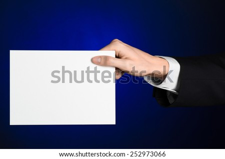 Business and advertising topic: Man in black suit holding a white blank card in his hand on a dark blue background in studio isolated - stock photo