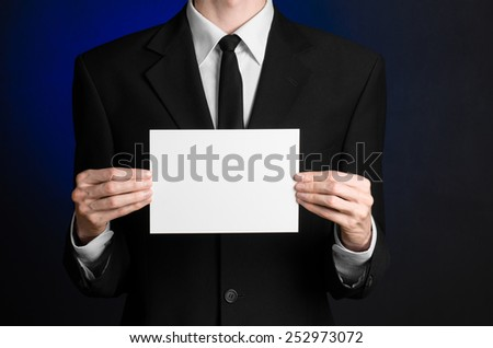 Business and advertising topic: Man in black suit holding a white blank card in his hand on a dark blue background in studio isolated
