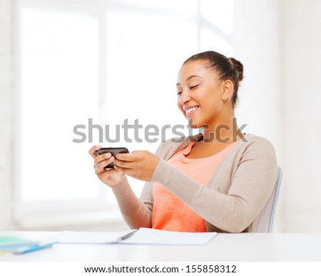 business, and communication concept - smiling african woman with smartphone in office