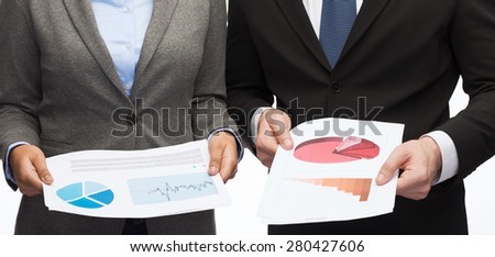 business and economy concept - smiling businesswoman and businessman with graphs and charts - stock photo