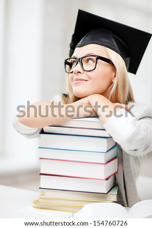 business and education concept - happy student in graduation cap with stack of books - stock photo