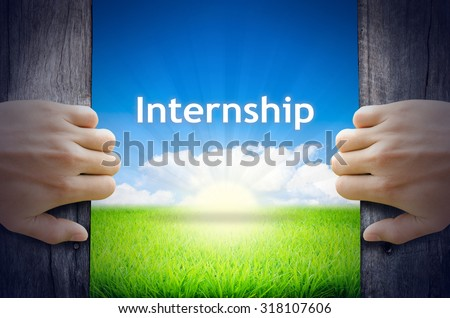"""Business and Education Concept """"Internship"""". Hands opening a wooden door then found a texts floating among new world as green grass field, Blue sky and the Sunrise. - stock photo"""
