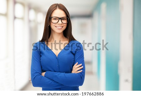 business and education concept - smiling businesswoman, teacher or student in glasses at school or office - stock photo