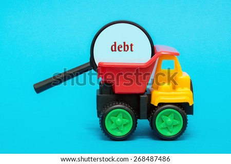 Business and finance concept. Toy lorry carrying a magnifying glass looking for word DEBT on blue background - stock photo