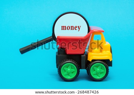 Business and finance concept. Toy lorry carrying a magnifying glass looking for word MONEY on blue background - stock photo