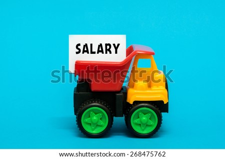 Business and finance concept. Toy lorry transporting a SALARY note on blue background. - stock photo