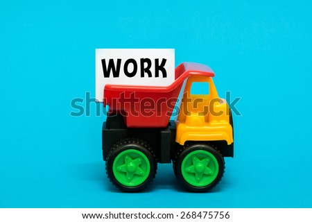Business and finance concept. Toy lorry transporting a WORK note on blue background. - stock photo