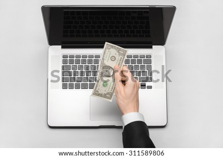 Business and freelance topic: hand in a black suit holding a banknote in the amount of 1 dollar on the background of a laptop on a white table in the studio isolated top view - stock photo
