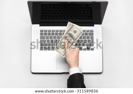 Business and freelance topic: hand in a black suit holding money dollars on a laptop on a white background table studio isolated top view - stock photo