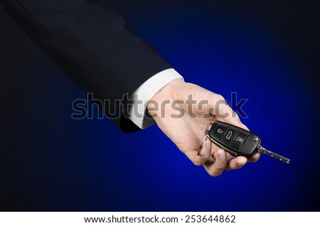 Business and gift theme: car salesman in a black suit holds the keys to a new car on a dark blue background in studio