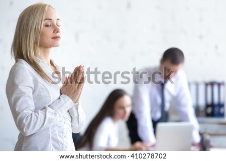 Business and healthy lifestyle concept. Beautiful young office woman meditating and relaxing with closed eyes at workplace. Attractive business lady using stress relief techniques at work. Copy space - stock photo