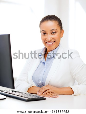 business and internet concept - smiling african businesswoman with computer in office - stock photo