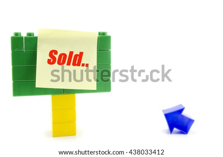 "Business and motivation concept, yellow sticky paper with word ""SOLD"" over plastic building blocks signage and blue arrow symbol isolated on white background"