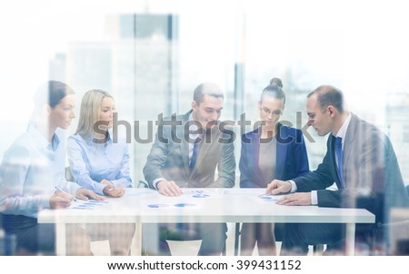 business and office concept - business team with documents having discussion in office - stock photo