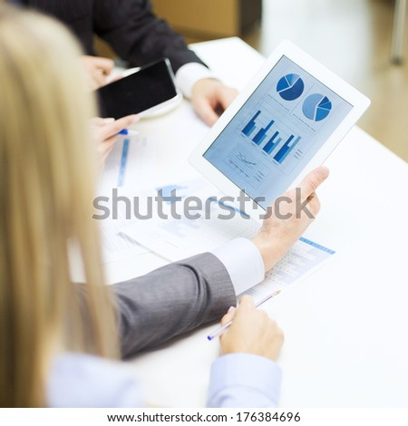 business and office concept - close up of business team with graph on tablet pc screen and coffee in office - stock photo