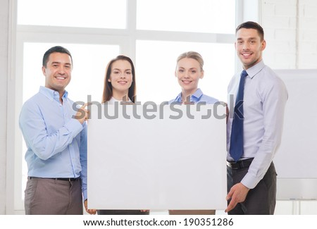 business and office concept - happy business team in office with white blank board - stock photo