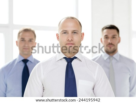 business and office concept - serious businessman in office with team on the back - stock photo
