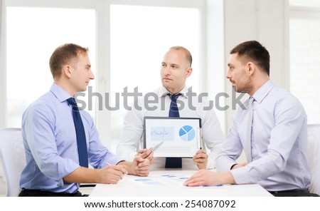 business and office concept - serious businessman showing others charts in office - stock photo