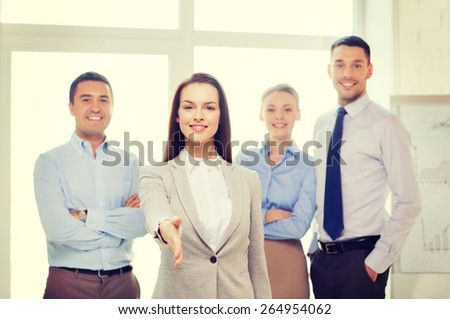business and office concept - smiling beautiful businesswoman ready for handshake with team in office