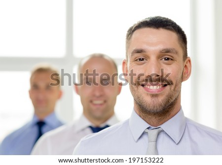 business and office concept - smiling businessman in office with team on the back