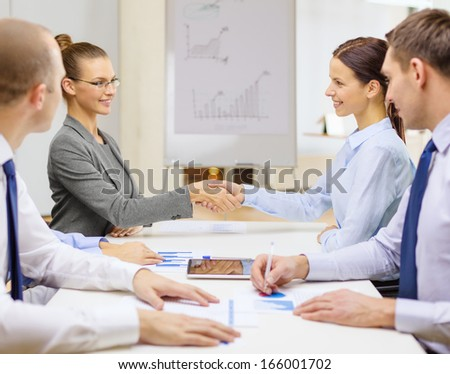business and office concept - two smiling businesswoman shaking hands in office - stock photo