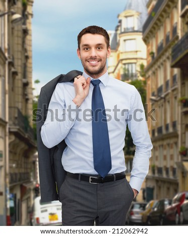 business and people concept - smiling young and handsome businessman over old city background