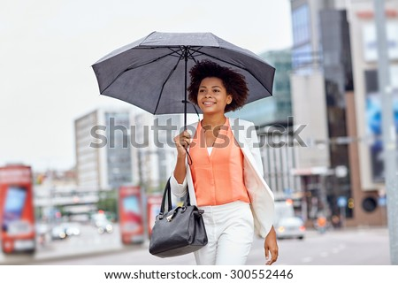 business and people concept - young smiling african american businesswoman with umbrella and handbag walking down city street - stock photo