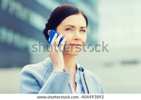business and people concept - young smiling businesswoman calling on smartphone over office building - stock photo