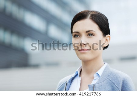 business and people concept - young smiling businesswoman over office building - stock photo