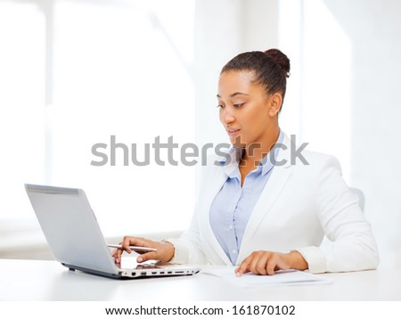 business and technology concept - african businesswoman with laptop writing something in notebook - stock photo