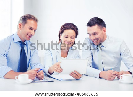 business and technology concept - business team looking at tablet pc in office