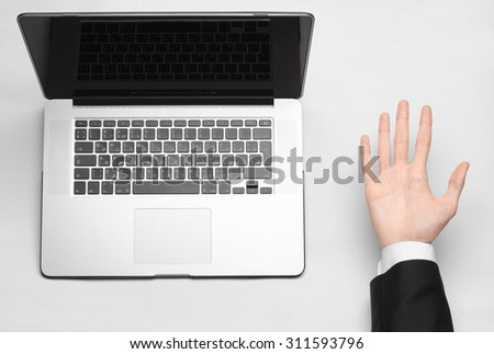 Business and technology topic: the hand of man in a black suit showing gesture against a gray and white background laptop in the studio isolated top view - stock photo