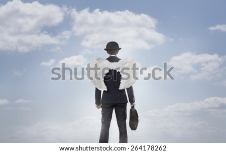 Business angel against the sky with copy space - stock photo